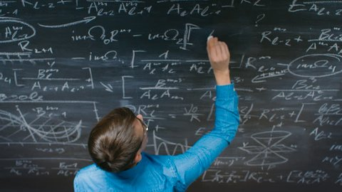 High-Angle Shot of a Brilliant Young Student Writing Complex Mathematical Formula/ Equation on the Blackboard. Shot on RED EPIC-W 8K Helium Cinema Camera.