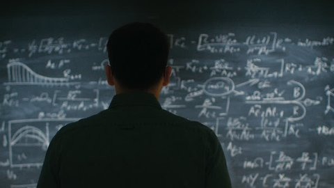 Brilliant Young Academic Approaches Blackboard with Complex Mathematical Formula Written on it, Starts Thinking about Solution. Shot on RED EPIC-W 8K Helium Cinema Camera.