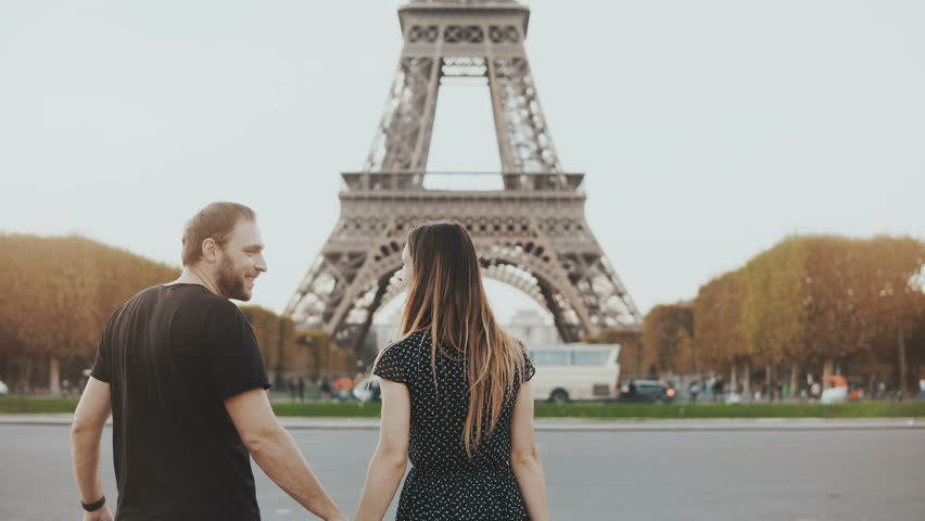 Young happy couple walking near the Eiffel tower in Paris, France. Man and woman hugging and kissing on the street.