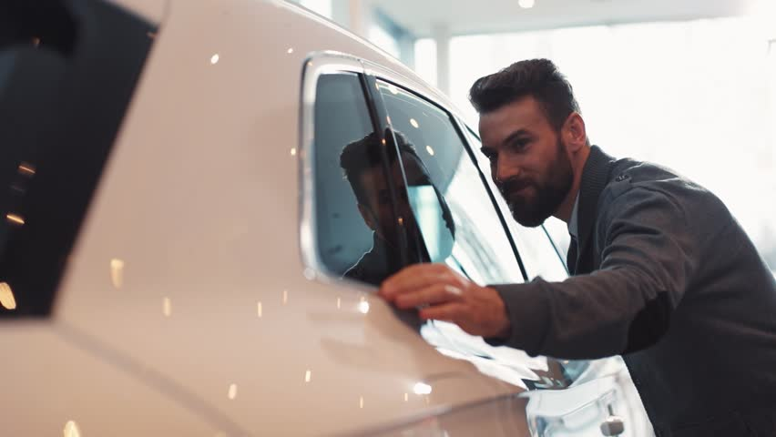 Young man with beard looking carefully at car in car dealership. Guy touching side window of beautiful shiny white car.   Shutterstock HD Video #1008067564