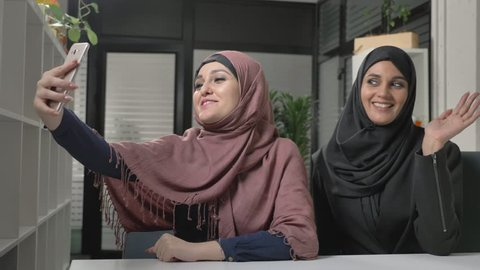 Two young beautiful girls in hijabs are sitting in the office and making selfies. Arab women in the office. Showing Hello sign in video chat. Waving their hands. 60 fps
