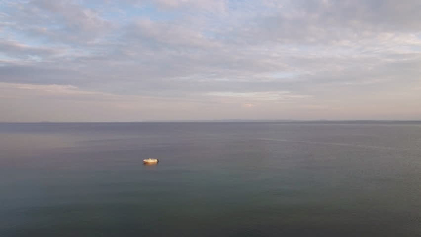 Aerial view of vast quiet sea with a single empty boat. Waterscape and cloudy sky | Shutterstock HD Video #1008085174