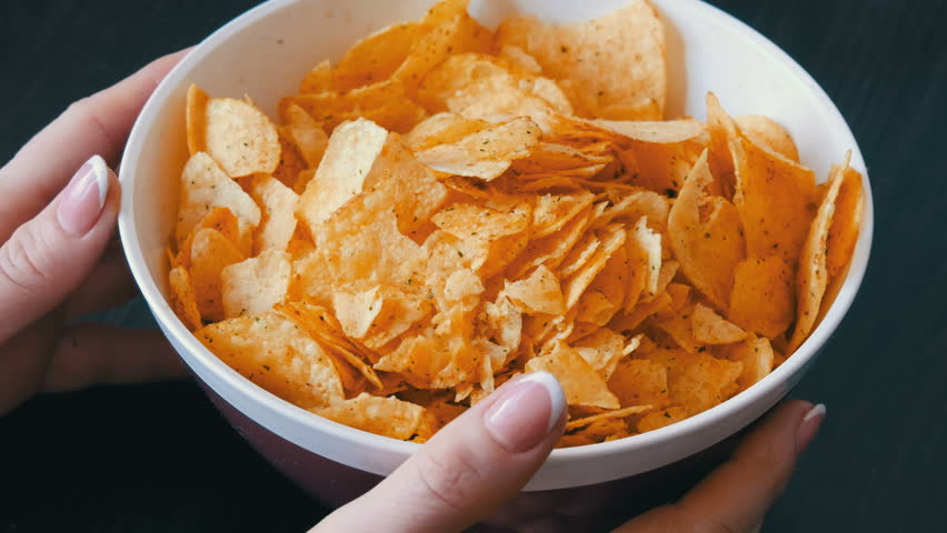 A large plate with potato chips on the table. Female hands with beautiful manicure take chips