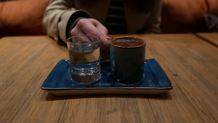 Woman take gulp of traditional Turkish coffee, closeup shot of cup and glass with pure water, standing on small plate on table. Dim lighting, blurred figure on background.