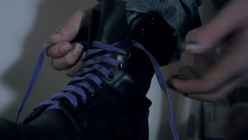 A person tying the shoelaces of a steel toed combat boot.