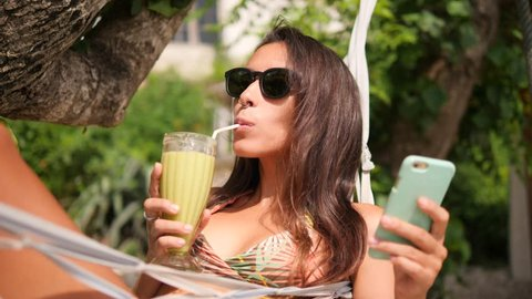 Mixed Race Young Tourist Woman Drinking Green Smoothie and Using Smartphone and Relaxing in Hammock on Tropical Island. Girl With Mobile Phone at the Beach. 4K, Slow Motion. Bali, Indonesia.