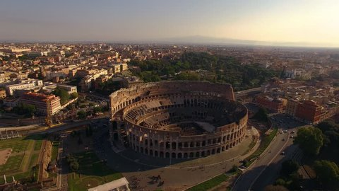 Beautiful cinematic aerial view of the Colosseum in Rome with the sunset on the horizon during golden hour