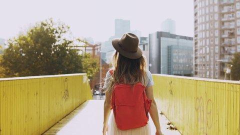 Excited girl in hat, long hair walks on a bridge. European female traveller happy, turn round between yellow walls. 4K.