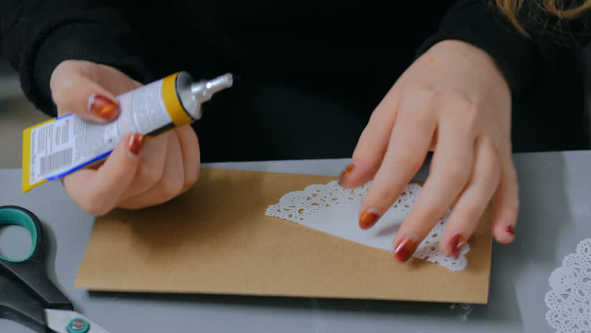 Professional woman decorator, designer working with kraft paper, applying glue and making envelope at workshop, studio. Design, handmade and art concept