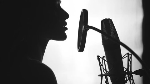 Young sexy profile of a woman with a beautiful face and lips. Girl singing to the microphone in a studio. Black and white