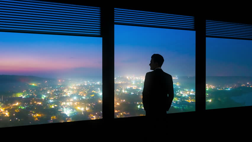 The man stand near a window on the night city background. time lapse