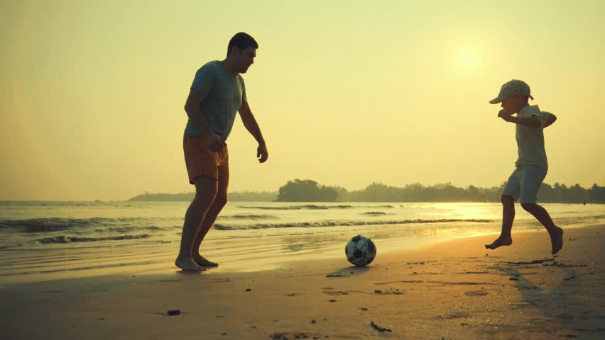 Father and son playing together with ball in football on the beach under sunset background #1008171754