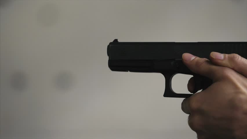 Gun is shot close-up. Pistol in hand close-up. Pistol being shot 1 times. Man shoots a black gun