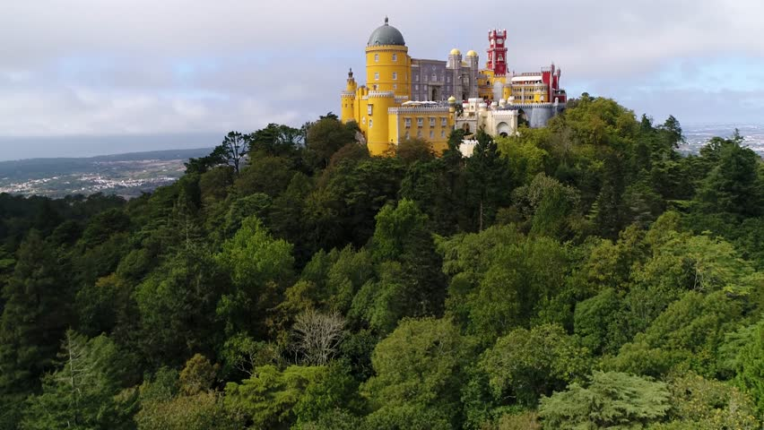 Aerial view of the iconic Pena National Palace moving up from forest originally built on Monastery of Nossa Senhora da Pena and renovated extensively through the initiative of Ferdinand II of Portugal