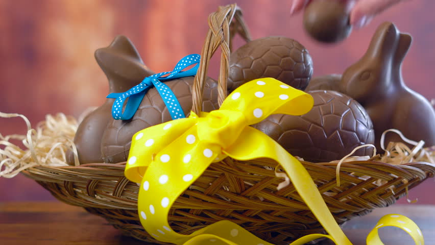 Happy Easter hamper of chocolate eggs and bunny rabbits in large basket with silk tulips on dark wood table, stacking eggs.