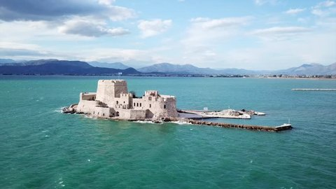 Aerial drone video from picturesque and famous venetian fortress and small islet of Bourtzi with views to iconic city of Nafplio former capital of Greece, Argolida, Peloponnese