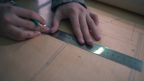 Close-up, The Boy Makes an Airmodel Drawing on Millimeter Paper with Pencil and Ruler