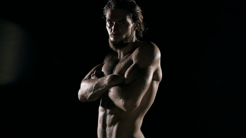Confident sport man portrait. Six packs fit man walking from black background. with shadow cast to the camera.