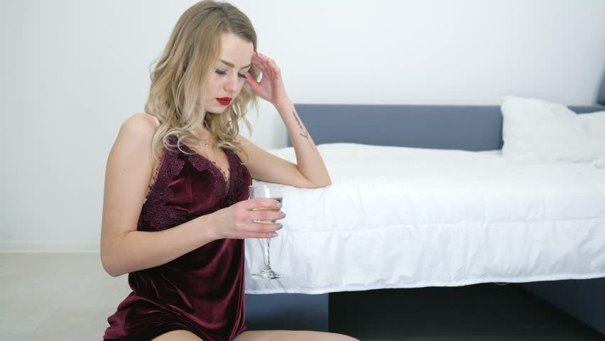 stress, a single upset beautiful young woman in nightdress drinks champagne while sitting on the floor near the bed