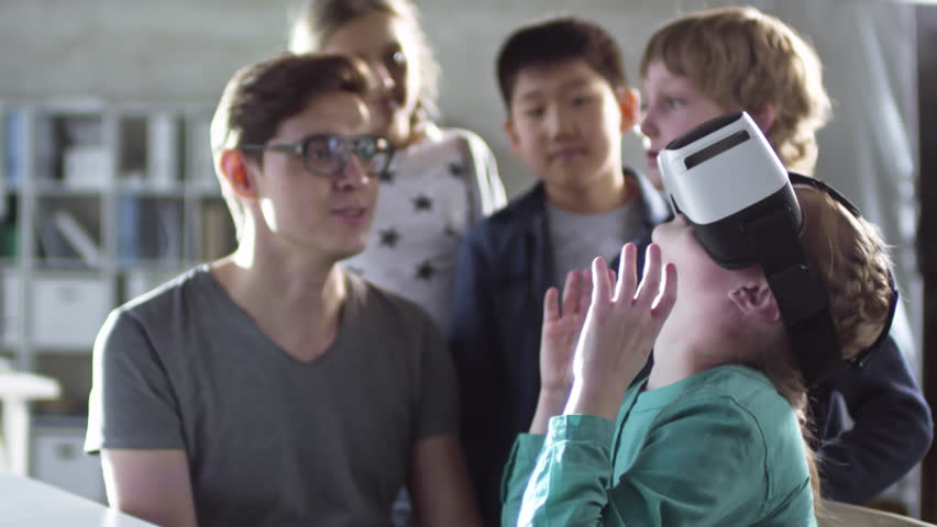 Teacher shows primary school children how to use virtual reality glasses during computer coding class, and they get excited