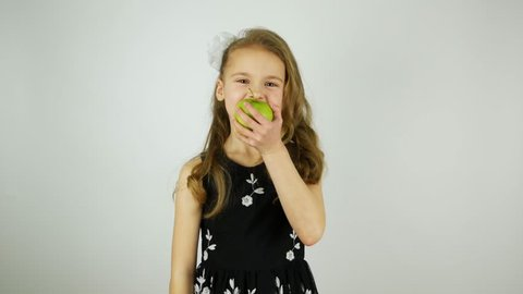 Smiling girl eats a green juicy apple and says Yum. Apple crunching when biting. Original sound