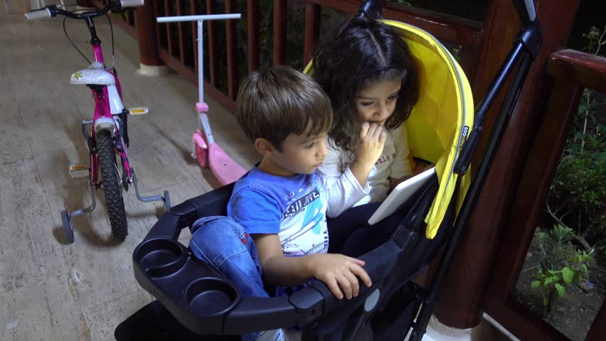 4K Kids watch tablet sitting together in one pushchair  | Shutterstock HD Video #1008283504