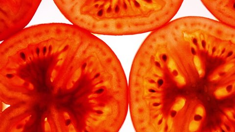 Excellent top view of sliced fresh red tomato, love apple, in flat lay close up, rotating clockwise with down center. Amazing vegetarian macro background with vibrant texture and backlight in UHD 4k.