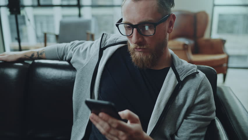 Attractive bearded man with smartphone sitting on sofa at modern loft home in the living room and chatting with friends. | Shutterstock HD Video #1008295954