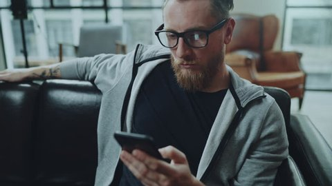 Attractive bearded man with smartphone sitting on sofa at modern loft home in the living room and chatting with friends.