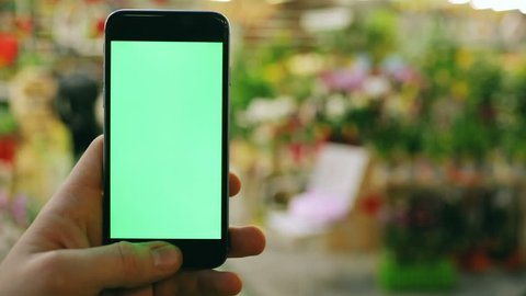 man using smart phone in flower shop on blur background / bokeh light market public space business sell colorful flowers digital device tapping display mock-up swapping mobile green screen chroma key
