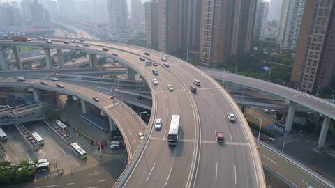 SHANGHAI, CHINA - MAY 5, 2017: Aerial view of Nanpu bridge highway junction. Cars moving by spiral, fog, sunny day.