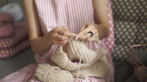 Close up female knitting hands. Woman knitting woolen sweater sitting on couch