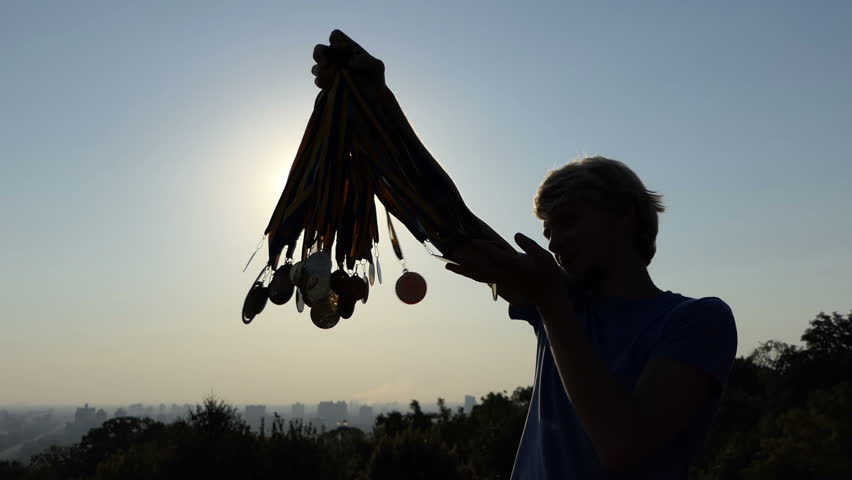 Talented man raises many medals at sunset in summer in slo-mo #1008334924
