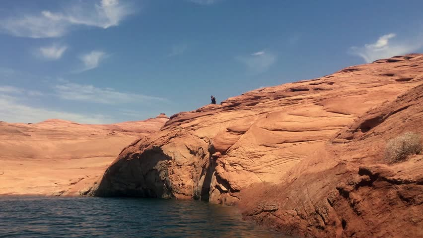 Lake Powell, Utah. A man jumps off of red rock cliff into the lake below. Lake Powell is a favorite destination for many activities, including cliff jumping.