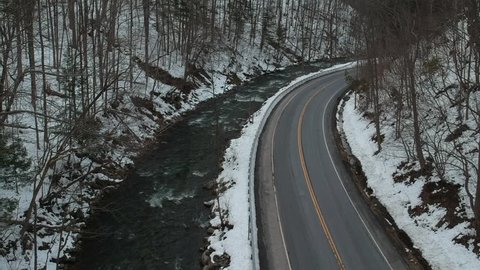 Aerial Drone Footage. Car driving down  winding back road next to River. Upstate New York, Winter 2018