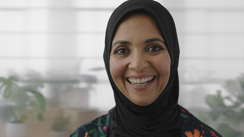 close up portrait of senior muslim business woman laughing cheerful looking at camera wearing traditional headscarf real people series #1008367114