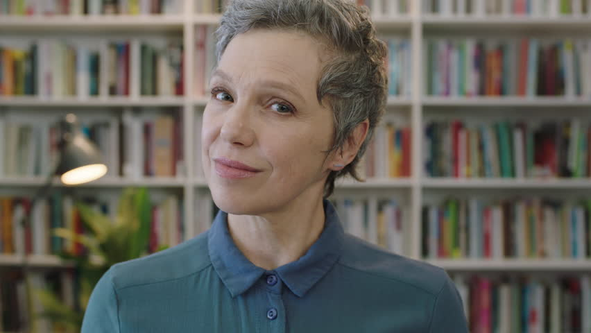 portrait of mature friendly caucasian woman librarian smiling looking confident at camera in library background real people series