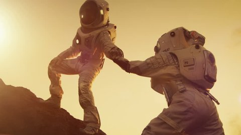 Two Astronauts Climbing Mountain Hill Helping Each Other, Reaching the Top. Overcoming Difficulties, Important Moment for the Human Race. Shot on RED EPIC-W 8K Helium Cinema Camera.