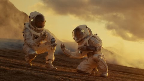 Two Astronauts Collect Soils Samples on Alien Planet, Analyzing Them with Hands Computer. Mars/ Red Planet Manned Expedition. Shot on RED EPIC-W 8K Helium Cinema Camera.
