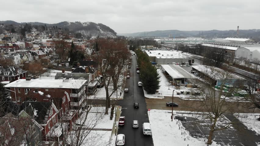 A slow forward aerial establishing shot of a small northeastern rust belt American town in the winter. Factories in the distance. Pittsburgh suburbs.