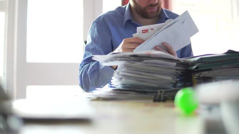 A Man In Debt Is Concerned And Stressed Looking Through Bill Letters 4K. Final Notice Warning Letter With Red Writing.