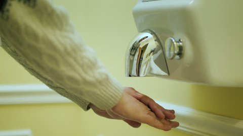 The man dries his hands under a stream of hot air. Hand dryer