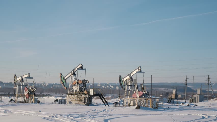 Working oil pumps in the winter field on the background of the city | Shutterstock HD Video #1008440854