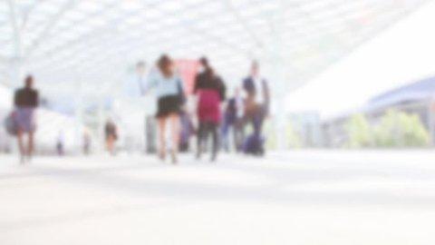 People join a trade show. Background with an intentional blur effect applied. Humans not recognizable.