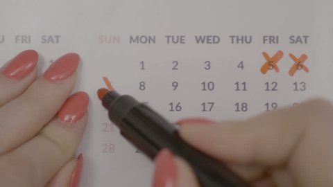 Top view of business woman hands crossing over monthly appointment dates on calendar agenda