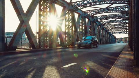 Zooming Time lapse of cars driving on the asphalt road of the city bridge on a sunny day in Dieppe, France. Metal structure of a bridge tunnel. Urban scene, city life, transport and traffic concept