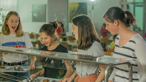 GRIZE, SLOVENIA - 10. JUNE 2017 Girls and boys are taking food in the school canteen. They are a bit hungry and are going to eat a snack and drink some tea.