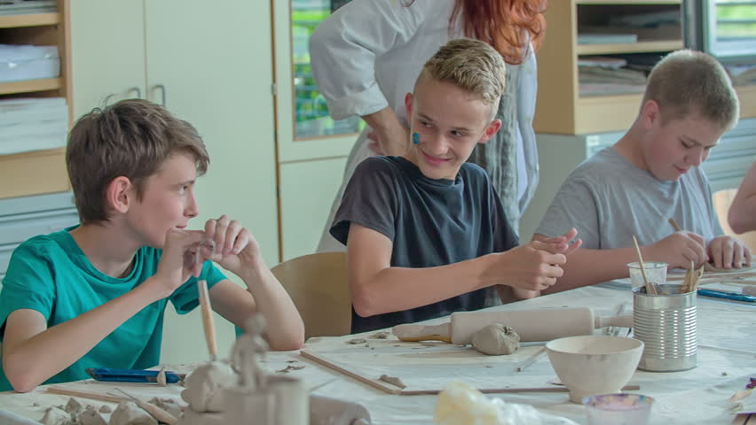 GRIZE, SLOVENIA - 10. JUNE 2017 Students are having an art class and they are painting. A girl teases one of the boys. The teacher is watching them. #1008514954