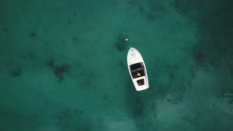 Overhead drone shot of small wooden rowing boat in pristine crystal clear blue waters of Croatian coastline, popular holiday destination in Europe