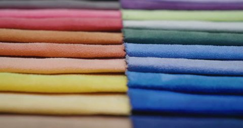 In a textile shop, there are fabrics of various colors and various materials, such as fabric, lace, satin, linen. Concept of: tailoring, colors, fabrics, clothes and fashion.
